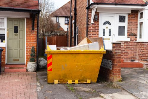 yellow skip bin for rubbish removal outside a home
