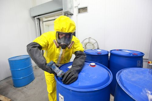 man in hazard suit getting rid of hazardous waste in blue containers
